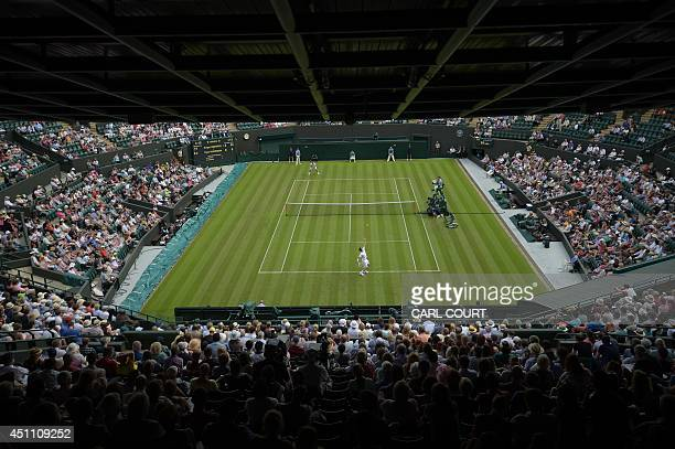 Bulgaria's Grigor Dimitrov serves to US player Ryan Harrison during their men's singles first round match on day one of the 2014 Wimbledon...