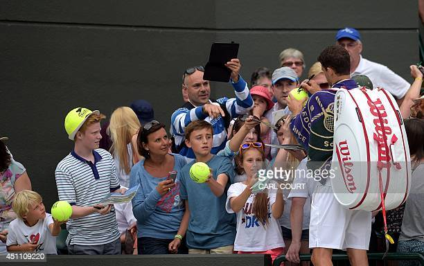 Bulgaria's Grigor Dimitrov signs his autograph to fans after winning his men's singles first round match against US player Ryan Harrison on day one...