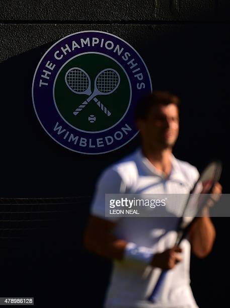 Bulgaria's Grigor Dimitrov stands in front of the official Wimbledon Championships logo as he plays against Argentina's Federico Delbonis during...