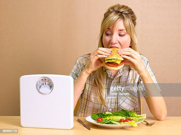 Bulimic girl eating burger with bathroom scales