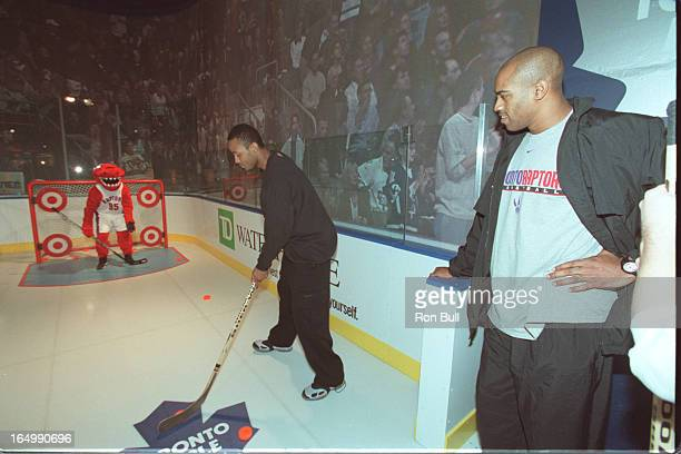 Bull 11/07/00 Fan Zone opened at ACC Vince Carter is amused as the raptors mascot slam dunks on a net set at the height for smaller children their...