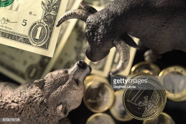 Bull and Bear among Dollar Bills and Euro Coins