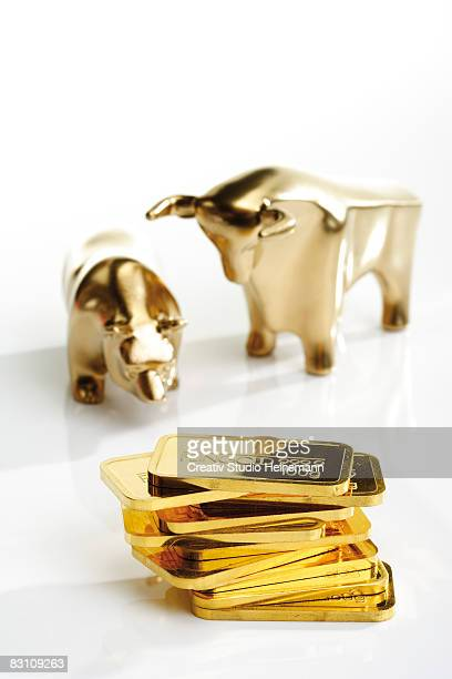 Stack of gold bars with bull and bear figurines