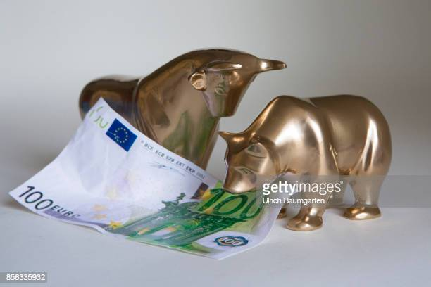 Bull and bear symbol for the ups and downs at the stock markets of the world The photo shows bull and bear with a 100 euro banknote