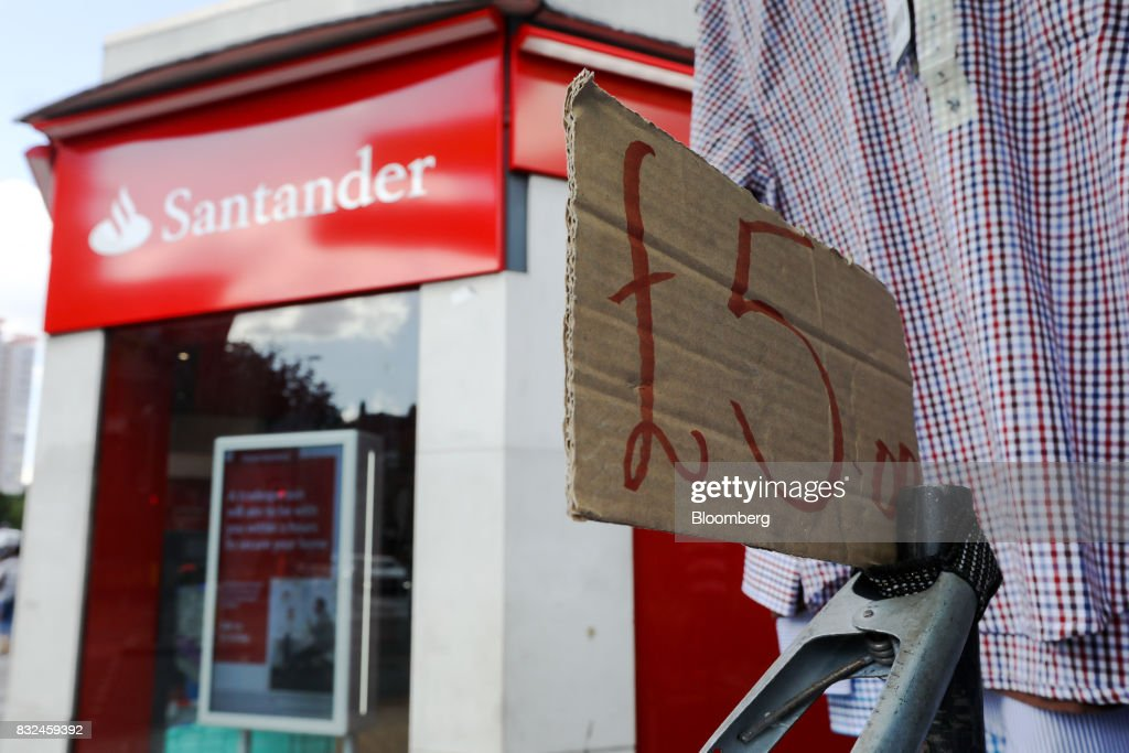 A bull dog clip holds a sign advertising a pound sterling price near a clothing rail at a market stall next to a bank branch of Banco Santander SA in London, U.K., on Tuesday, Aug. 15, 2017. Banco Santander, Spains biggest lender, has bought minority stakes in three financial-technology firms as ChairmanAna Botinmakes machine learning a hallmark of her growth plan. Photographer: Luke MacGregor/Bloomberg via Getty Images