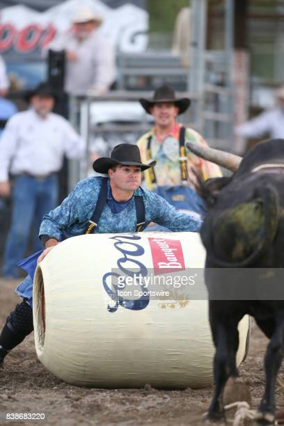 A bull fighter uses the rodeo barrel to distract the bull Black Out during the second round of the PRCA Pro Rodeo Extreme Bulls 'Beauty and the...