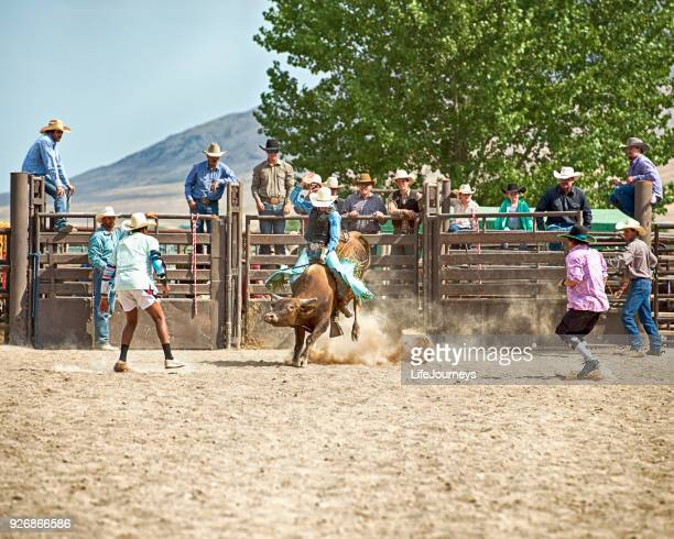 Bull Rider In The Middle of A Great Ride - Friends Behind Him In The Chutes Cheer Him On At A Rodeo Competition Event