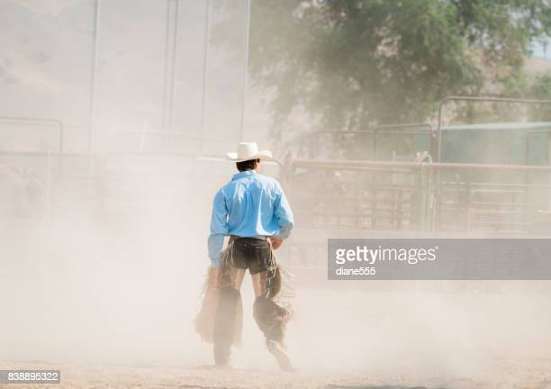 Bull Rider Walks Through The Dust After His Ride