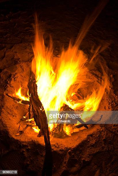 A camp fire blazes in the safety of the sand of a dry riverbed.
