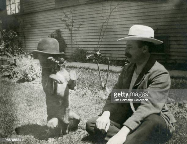 Bulldog stands on his hind legs with a bowler hat and pipe in his mouth, as a man sits in the grass nearby observing the scene, circa 1922.