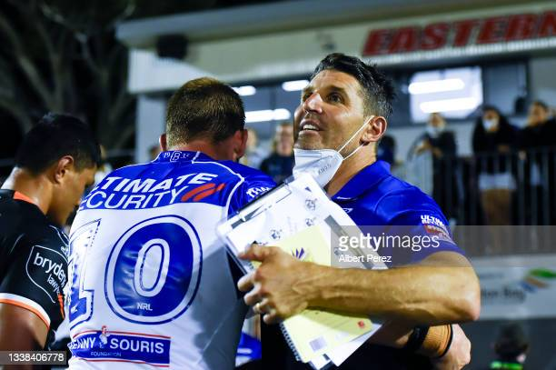 Bulldogs coach Trent Barrett embraces Jack Hetherington after his team's victory during the round 25 NRL match between the Wests Tigers and the...