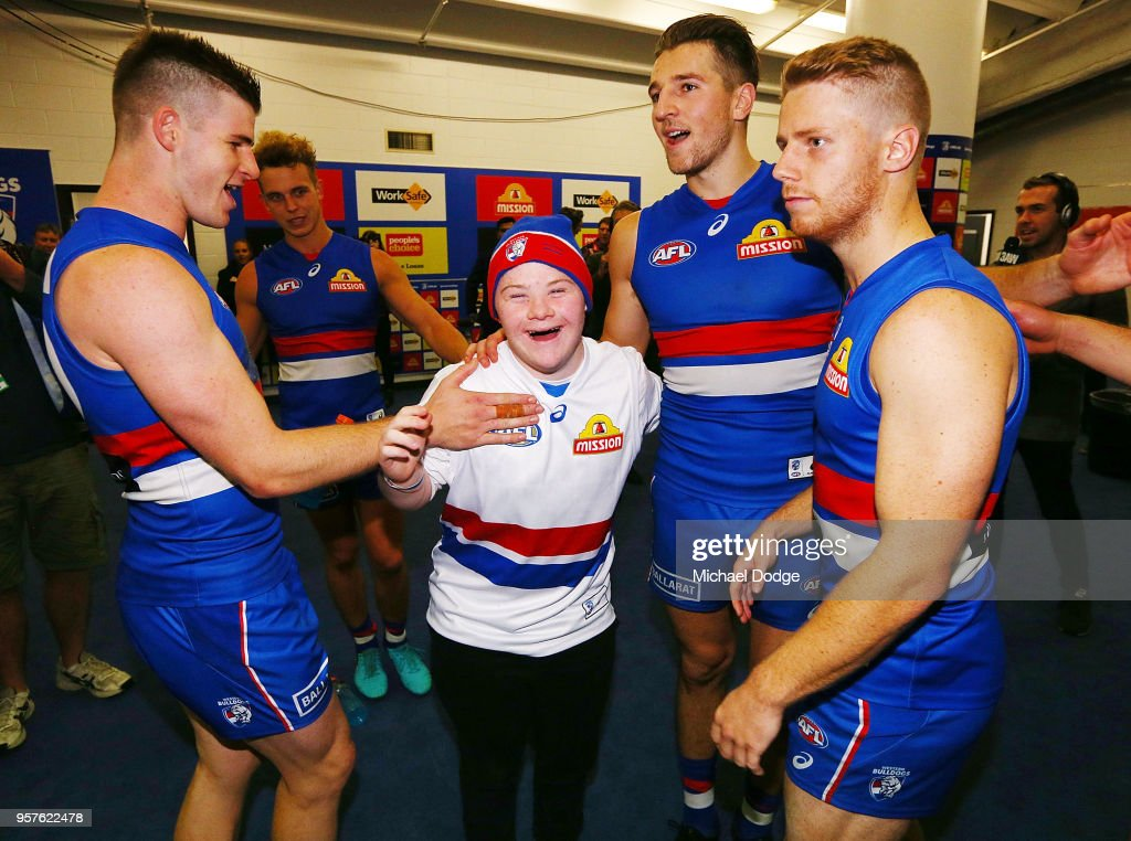 A Bulldogs fan sing the club song after winning with Billy Gowers (L) Marcus Bontempelli (C) and Lachie Hunter of the Bulldogs (R) during the round eight AFL match between the Western Bulldogs and the Brisbane Lions at Etihad Stadium on May 12, 2018 in Melbourne, Australia.