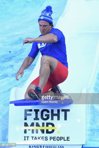 Bulldogs head coach Luke Beveridge goes down the Freeze MND slide during the round 12 AFL match between the Melbourne Demons and the Collingwood...