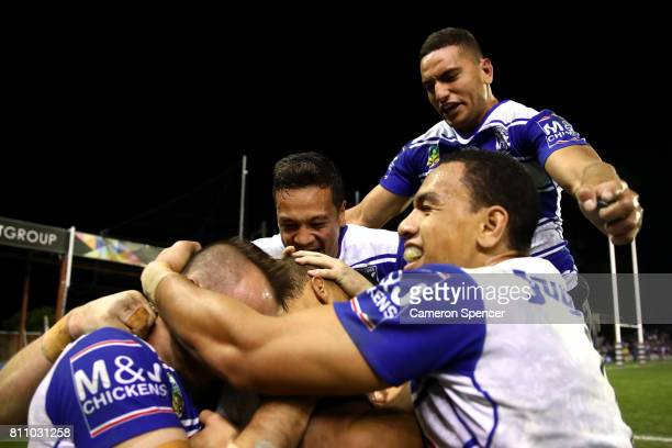 Bulldogs players embrace team mate Moses Mbye of the Bulldogs after scoring the winning try during the round 18 NRL match between the Canterbury...
