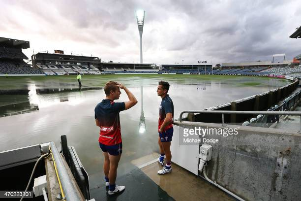 Bulldogs players Lachie Hunter and Luke Dahlhaus look at the ground that is under water after a storm passed through before the round two AFL NAB...
