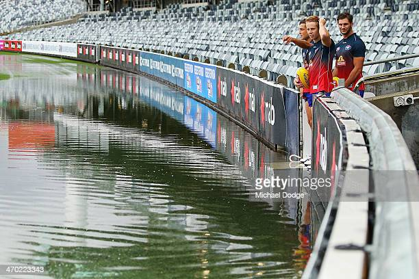 Bulldogs players Luke Dahlhaus Lachie Hunter and Koby Stevens look at the ground that is under water after a storm passed through before the round...