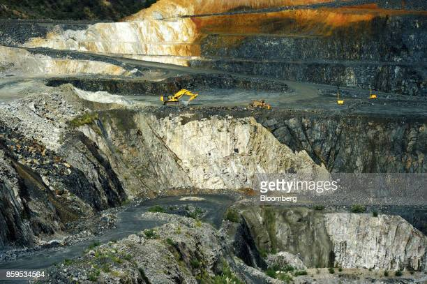 A bulldozer and excavator operate in an open pit mine at a Talison Lithium Ltd site a joint venture between Tianqi Lithium Corp and Albemarle Corp in...
