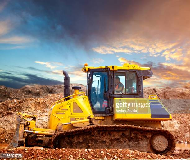 bulldozer at the construction site in the evening - caterpillar stock pictures, royalty-free photos & images