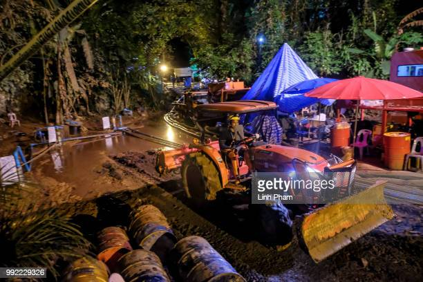 A bulldozer clear out the surface of the drilling well site at the entrance of Tham Luang Nang Non cave to release water in the effort of lowering...