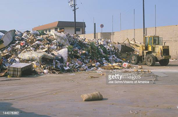 A bulldozer clearing a large pile of trash at a dump yard