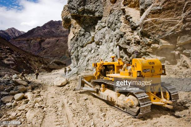 Bulldozer clearing boulders on National Highway 1 in Ladakh. The workers were blasting rocks with dynamite to widen the road in a narrow gorge....