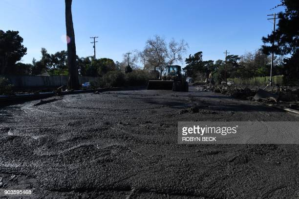 TOPSHOT A bulldozer clears mud from the northbound 101 freeway near Montecito after a massive mudslide in Montecito California January 10 2018...