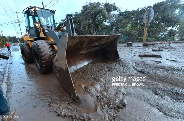 A bulldozer clears mud off the road near a flooded section of US 101 freeway near the San Ysidro exit in Montecito California on January 9 2018...
