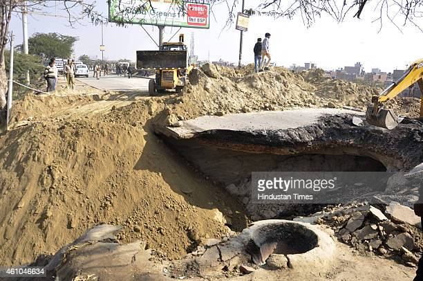 A bulldozer clears the debris after part of a road caved in at the NH24 Vijaya Nagar bypass near the Hindon river bridge in early morning due to a...