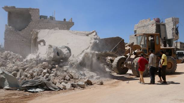 A Bulldozer Clears The Rubble Of A Building Destroyed During A