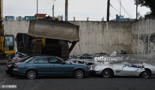 A bulldozer crushes luxury vehicles at a ceremony at the customs yard in Manila on February 6 after they were seized for being smuggled illegally...