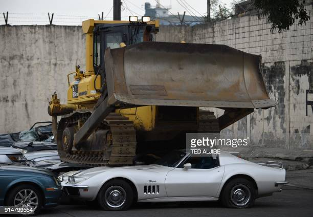 TOPSHOT A bulldozer crushes luxury vehicles at a ceremony at the customs yard in Manila on February 6 after they were seized for being smuggled...