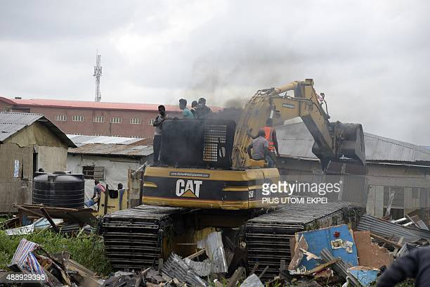 A bulldozer demolishes a house following a court ruling which forcefully evicted residents of Badiya community at Ijora distict of Lagos on September...