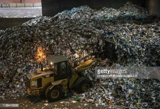 Bulldozer fills containers with recyclable materials at the Syctom waste sorting centre in Nanterre, on the outskirts of Paris, on April 25, 2019. -...
