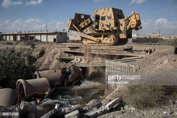 A bulldozer helping to clear the damaged streets crosses a bridge in the western neighborhood of Jazrah on the outskirts of Raqqa on October 30 2017...