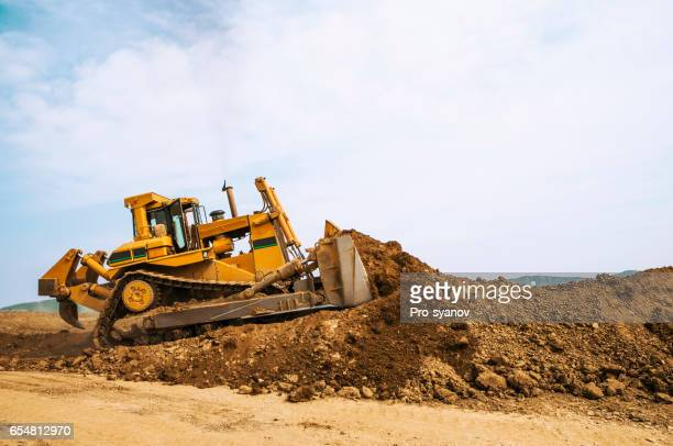 bulldozer in open field operation - excavator stock photos and pictures