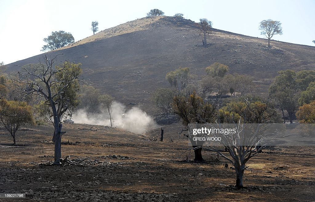 A bulldozer (C) is used in a paddock blackened by recent bushfires near Bookham, a small village in the Yass Shire in the southern region of Australia's New South Wales state, on January 10, 2013. Fires have been raging across Australia for nearly a week and while many have been contained, 126 are still burning and at least 15 remain out of control in the country's most populous state, New South Wales. AFP PHOTO / Greg WOOD