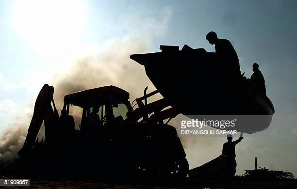 A bulldozer lifts a fishing boat as part of operations to clear tsunamiaffected areas in Therukapattu village some 50 km south of Madras 03 January...