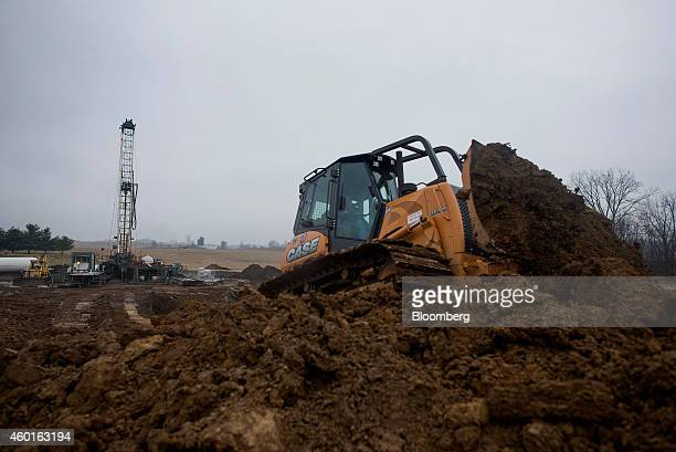 A bulldozer moves dirt to make another pit at a Knox Energy Inc oil drilling site in Knox County Ohio US on Monday Dec 8 2014 Explorers in the US...