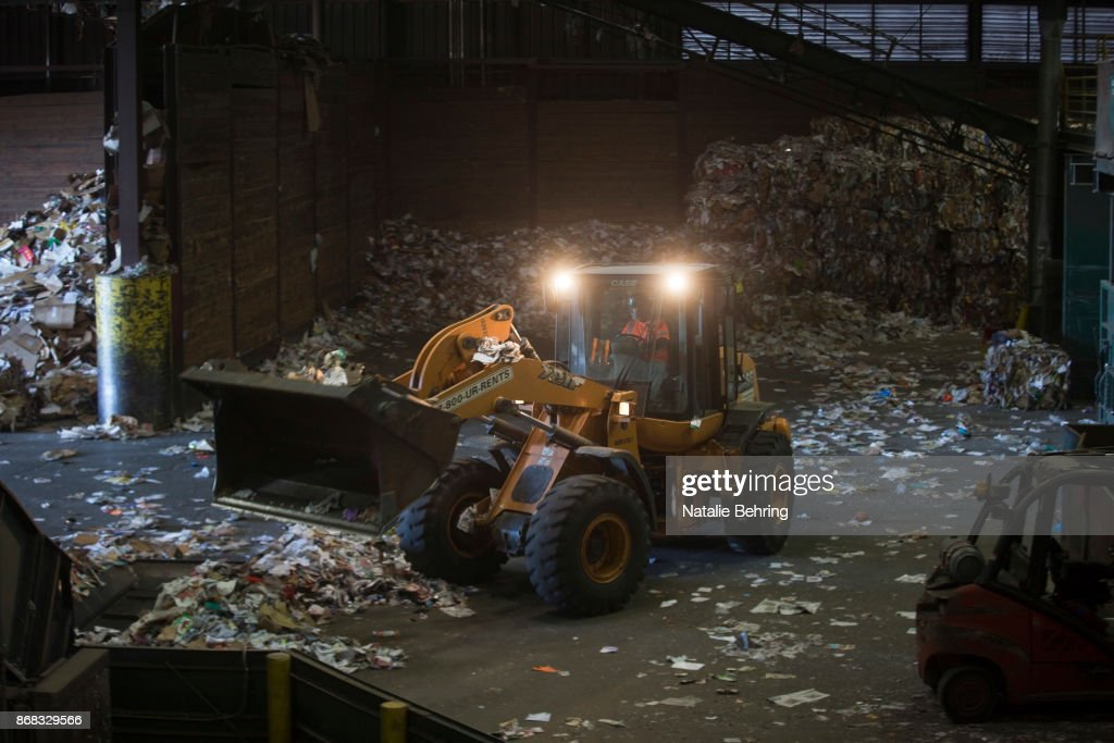 A bulldozer moves paper and plastic waste at Far West Recycling October 30, 2017 in Hillsboro, Oregon. For decades, shipping containers have been loaded with American scrap and waste and dispatched to China for recycling. But, the Chinese government is cracking down, and will no longer allow shipments of much of the mixed plastic and paper Americans throw in to recycling bins. The result of the ban may be more plastic in American landfills.