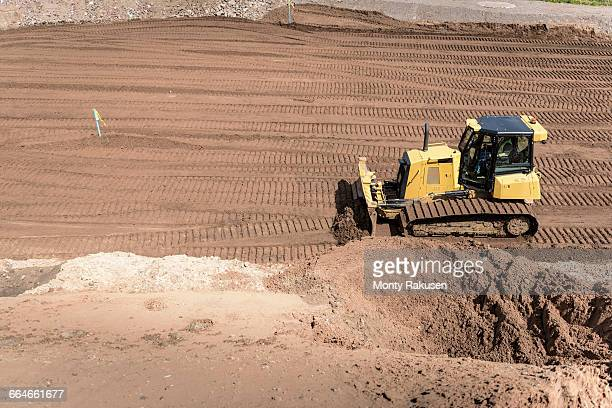 Bulldozer moving earth on housing building site