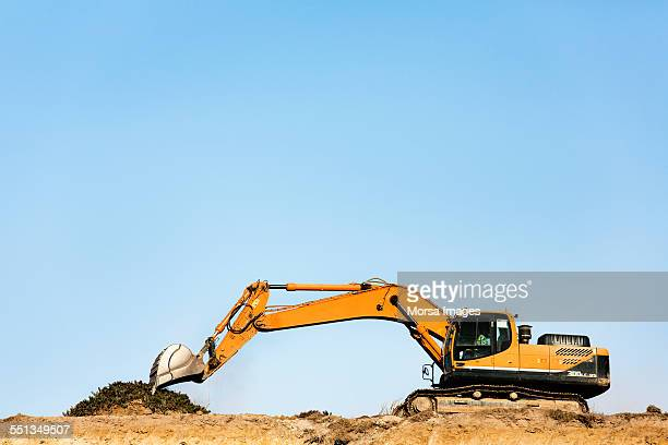 Bulldozer on quarry against clear blue sky