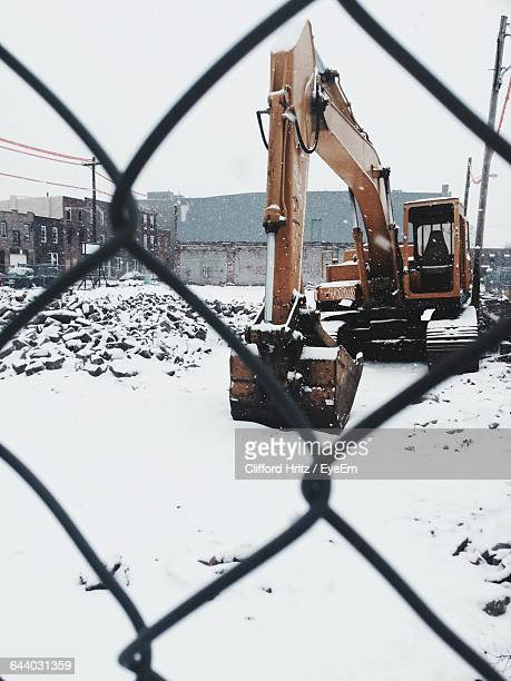 Bulldozer On Snow Covered Construction Site Against Sky Seen Through Fence