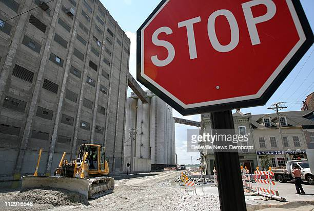 A bulldozer pushes ground rock which is being added to elevate Broadway above the rising Mississippi River flood waters in downtown Alton Illinois...