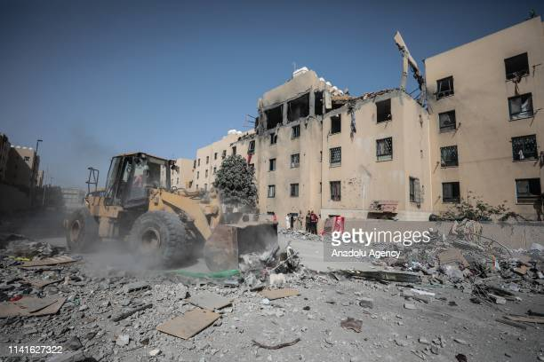 Bulldozer removes the debris near damaged buildings after Israeli attacks in Sheikh Zayed region near Gaza City, Gaza on May 06, 2019.