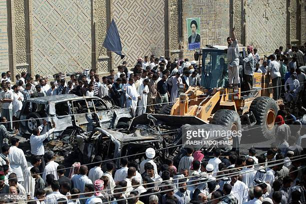 A bulldozer removes the destroyed vehicle of assassinated top Shiite leader Ayatollah Mohammad Baqer alHakim seen outside the Shrine of Imam Ali in...