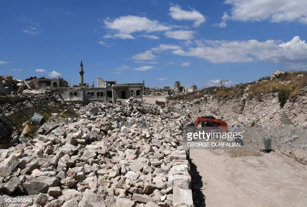 A bulldozer shifts rubble as Syrians restore the area of alSaffahiyah in the old city of Aleppo on April 22 2018 Following a suffocating siege and...