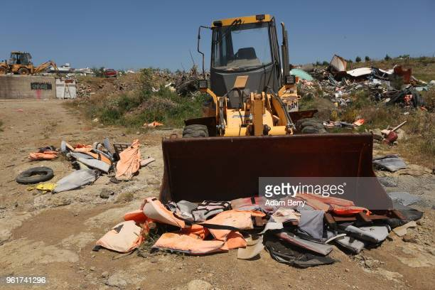 A bulldozer sits amidst piles of discarded life preservers used by refugees in their attempted crossings from Turkey to Greece on the island of...