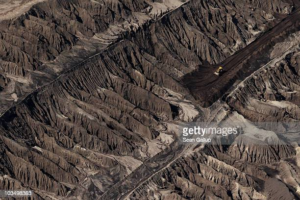 A bulldozer stands in jagged terrain at the openpit coal mine at Jaenschwalde on August 20 2010 near Cottbus Germany Though Germany is investing...