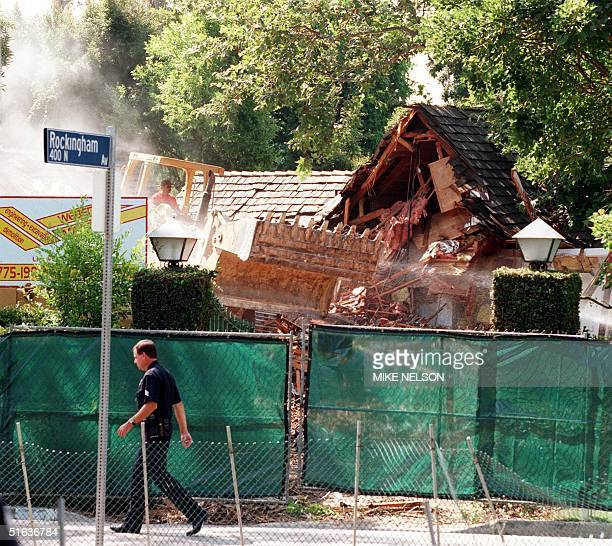 A bulldozer tears down the former residence of exfootball star OJ Simpson 28 July in Brentwood California The residence was the site of intensive...