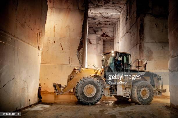 bulldozer arbeiten im unterirdischen marmorbruch - unterirdisch stock-fotos und bilder